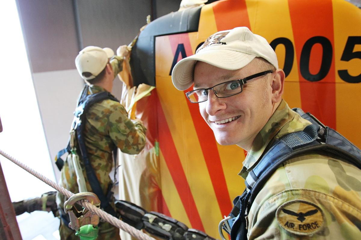 Aircraft surface finisher Corporal Kelvin Green is all smiles as the tail art on a No. 37 squadron C-130H Hercules is unmasked.